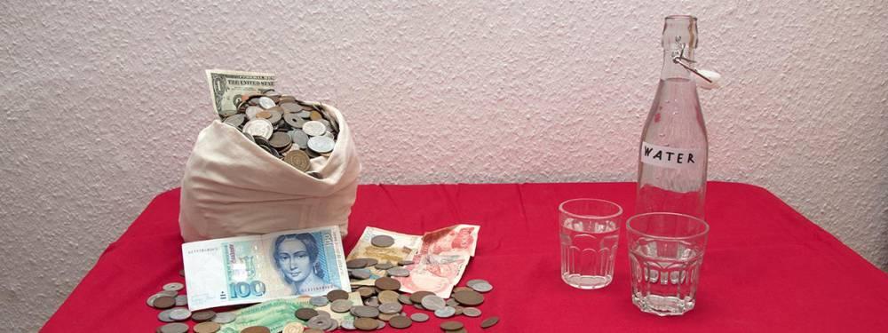 Ein Berg Schlafmünzen neben einer Flasche und Gläsern mit Trinkwasser