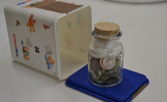 Eine Milchpulverbox und ein Tintenfass voll mit Münzen